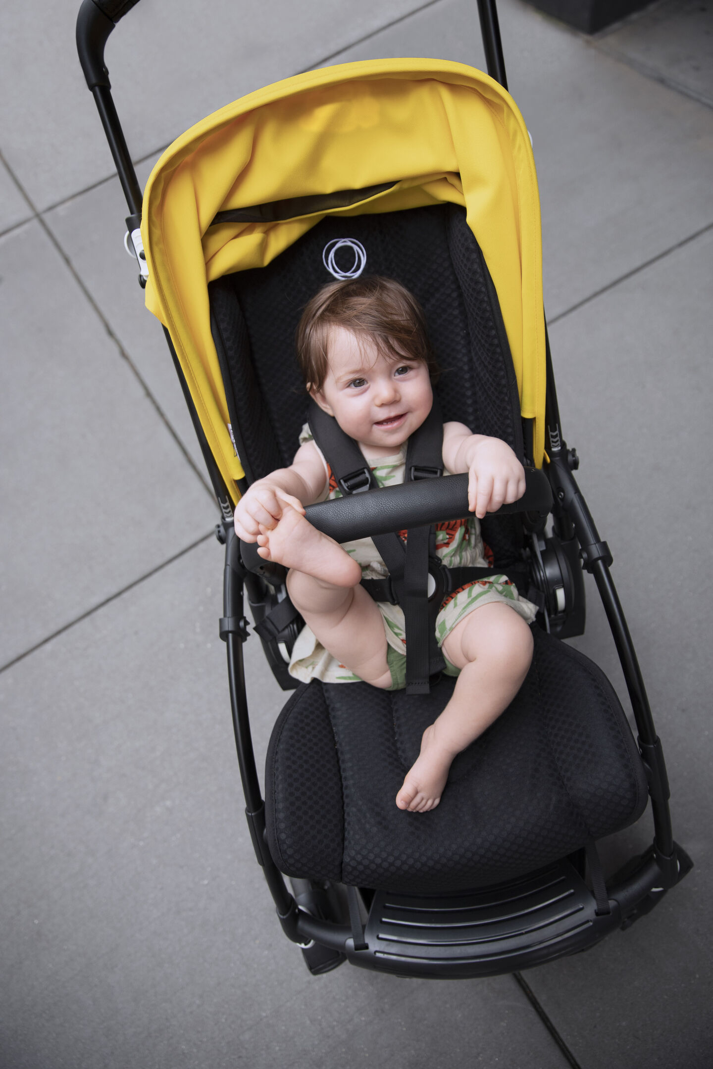 A child sitting in their Bugaboo Bee 6 stroller featuring a yellow sun canopy. Bugaboo newborn stroller accessories highlight.