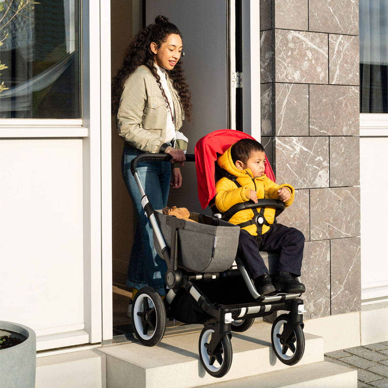 Woman pushing stroller through doorway