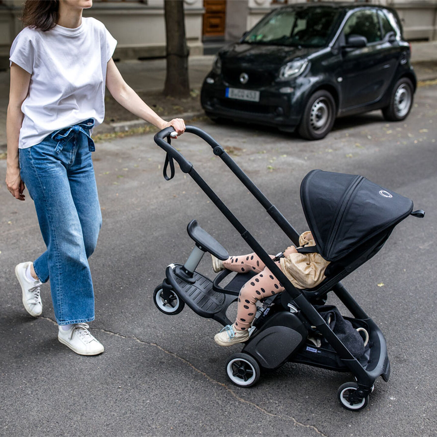 Woman pushing Ant stroller with one hand
