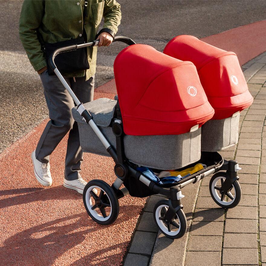 Man pushing stroller up curb