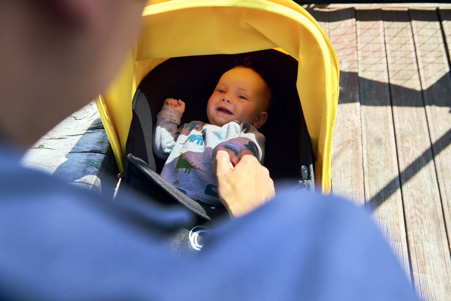 A baby happily smiling in their Bugaboo Bee 6 stroller featuring a yellow sun canopy. Bugaboo newborn stroller accessories highlight