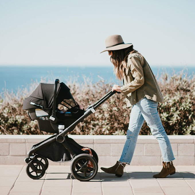 Woman pushing stroller with car seat attached