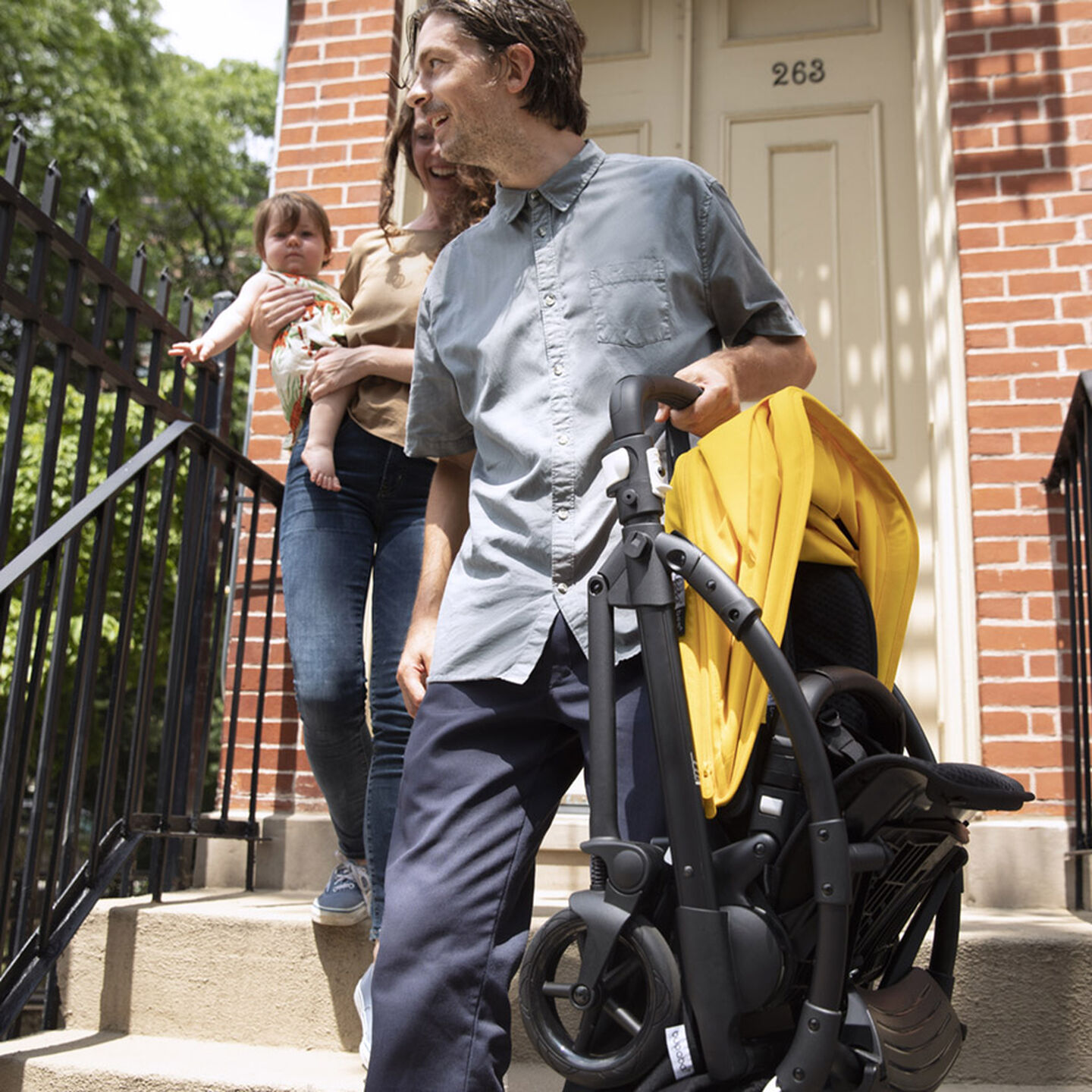 Man carrying folded Bee 6 stroller down stairs
