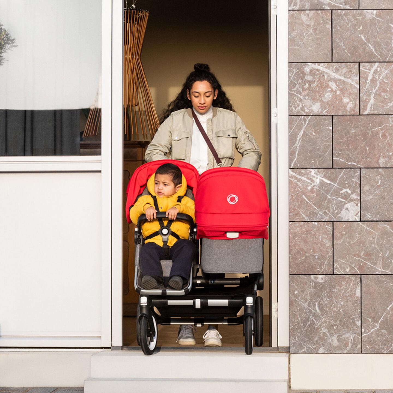 Woman pushing Donkey 3 Duo stroller through doorway