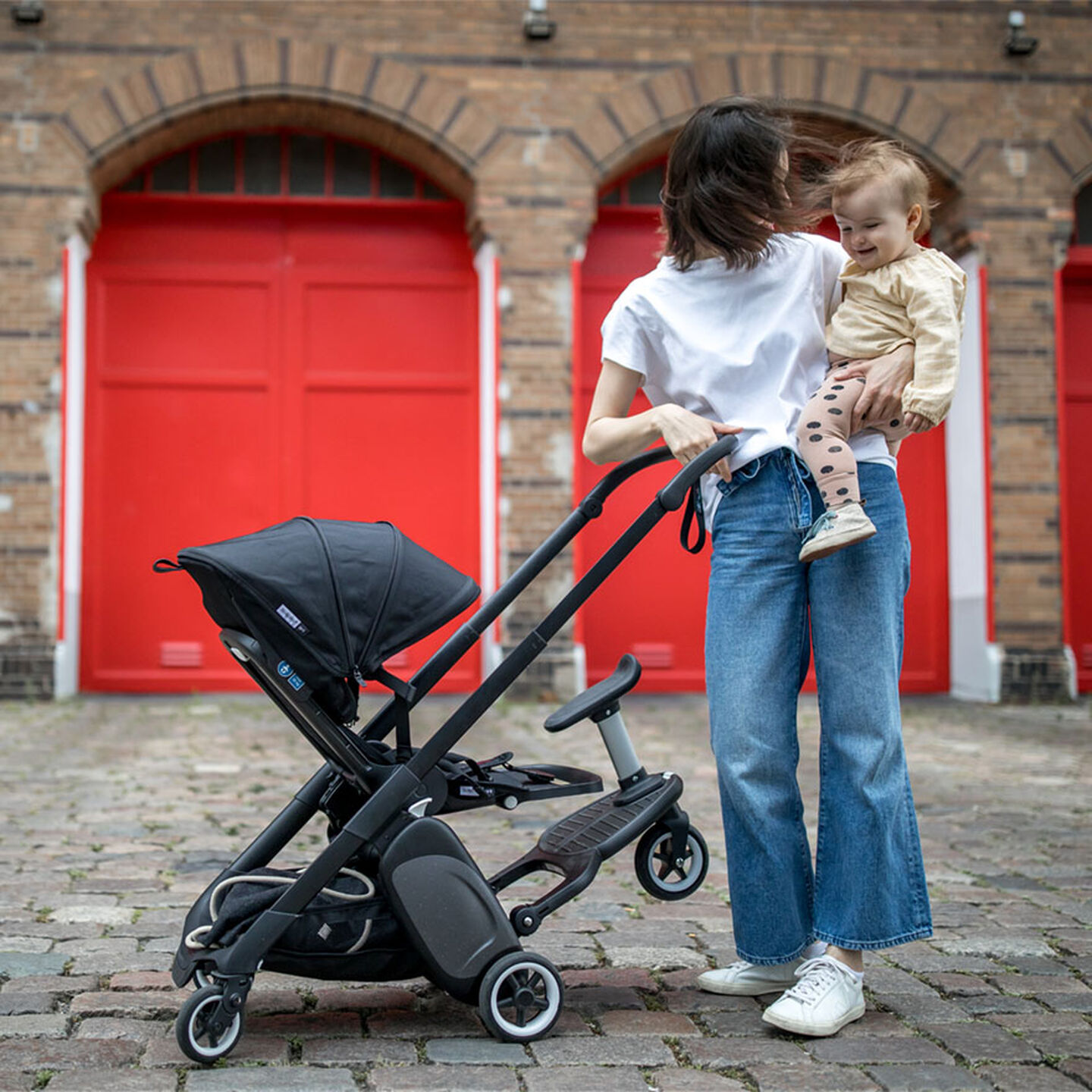 Woman with stroller holding child