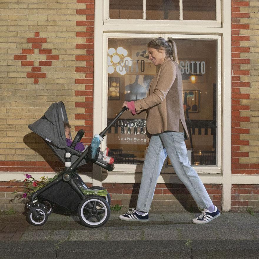 Woman pushing Lynx stroller on sidewalk