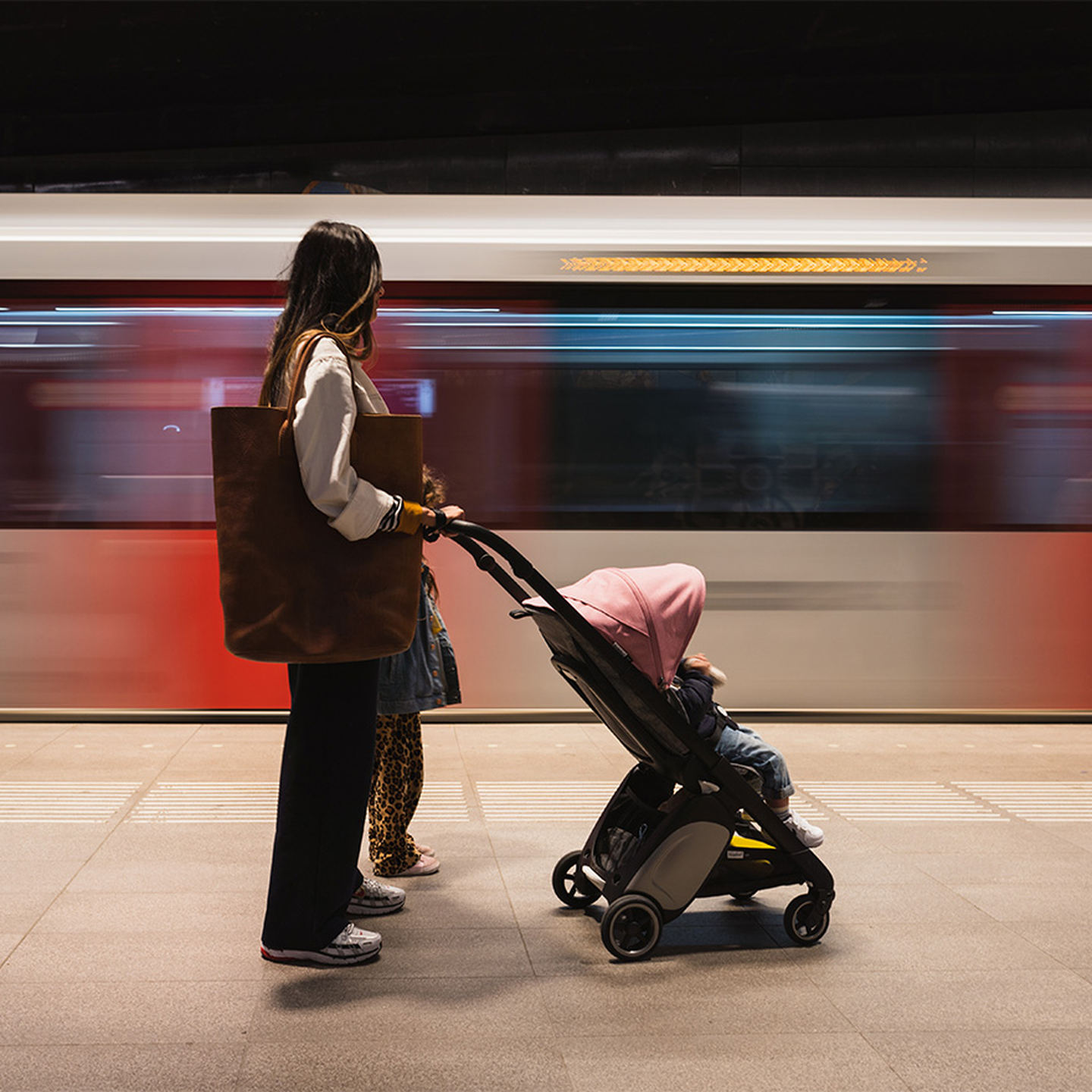Woman waiting for subway with Ant stroller