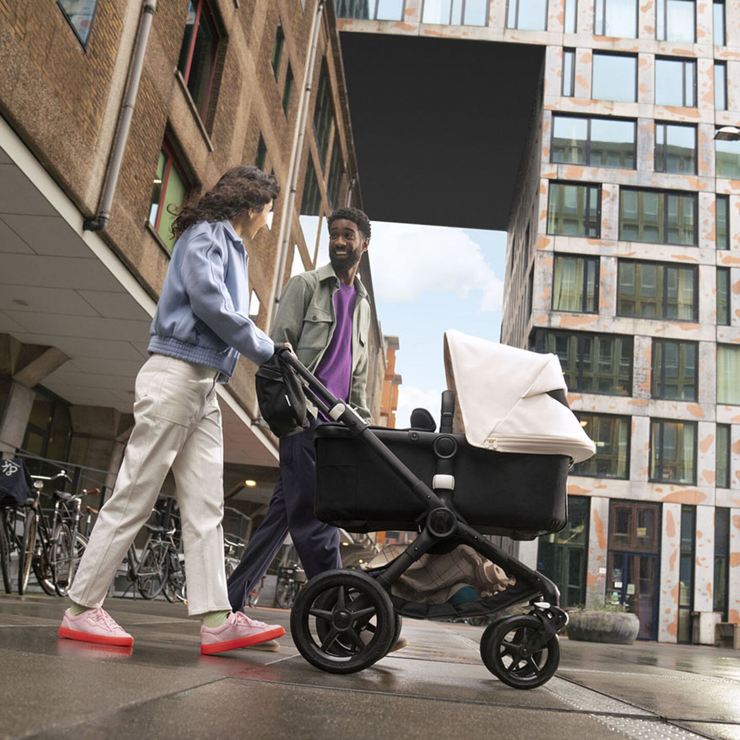 Man and woman with stroller in city