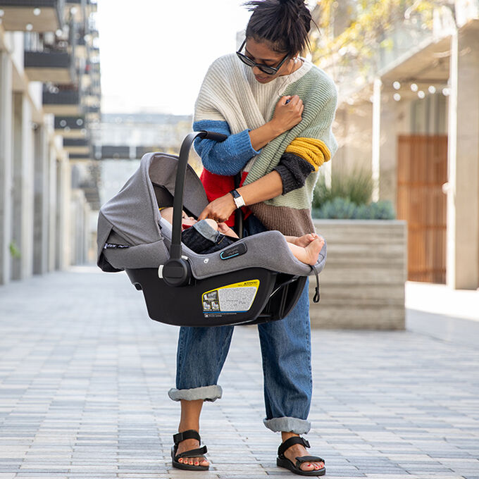 Woman carrying Turtle Air by Nuna car seat