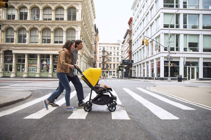 A couple crossing the street with their Bugaboo Bee 6 city stroller in the seat configuration